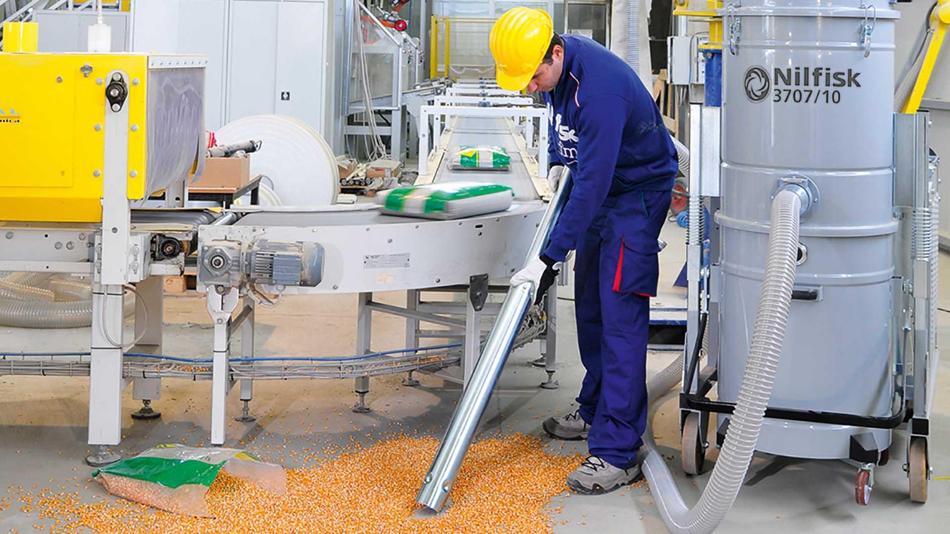 man vacuuming in industrial factory